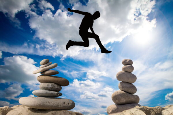 Man jumping above balance stones photo free download
